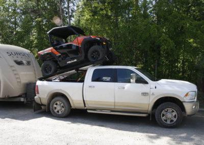 Un pick-up qui transporte un véhicule et tire une caravane.